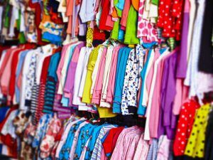 Colorful baby clothes hanging on hangers in a store
